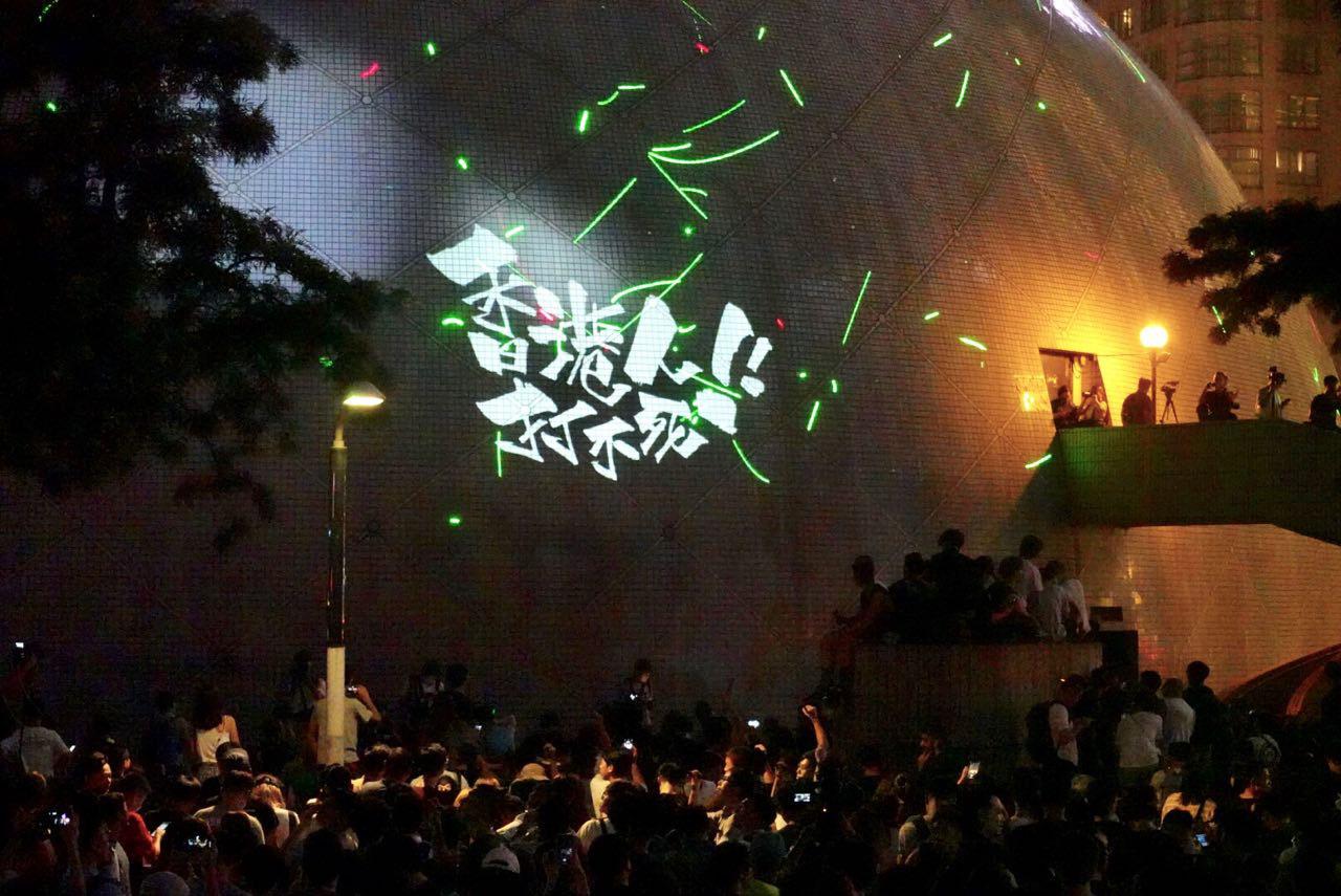 昨日近千名市民手持觀星筆在太空館外聚集,用觀星筆照射太空館、天空或附近的建築物。又有有市民以投射器在太空館外牆上投射「香港人打不死」等各種影像和標語。(宋碧龍/大紀元)