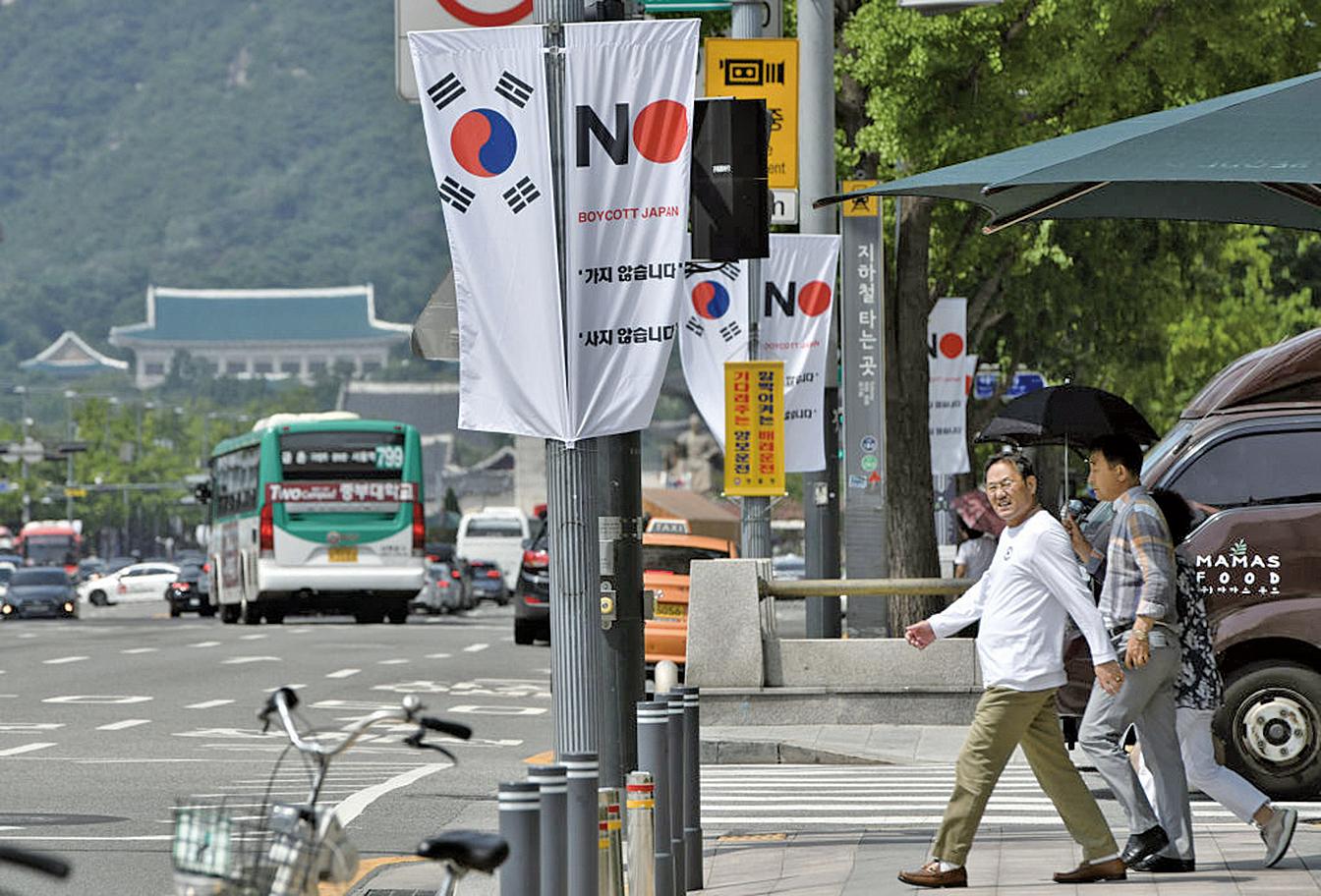 2019年8月6日,位於首爾中區的一條街道上,豎立南韓國旗(左)和寫著「抵制日本」(右)橫幅。(AFP)