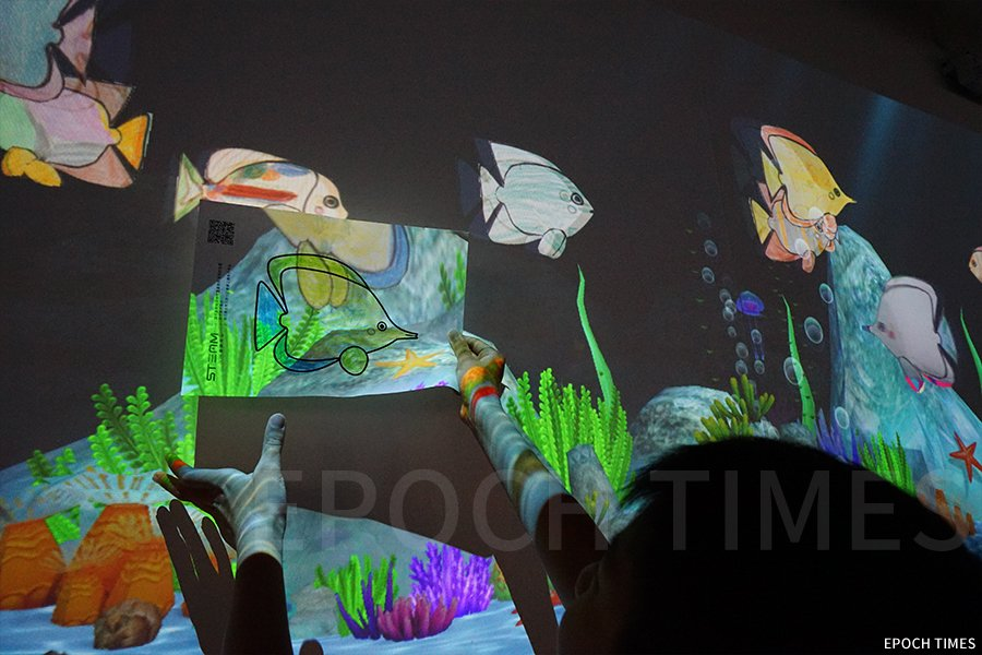STEAM VR館特色活動——AR主題互動水族館,學生將畫的魚送上電子魚缸。(曾蓮/大紀元)