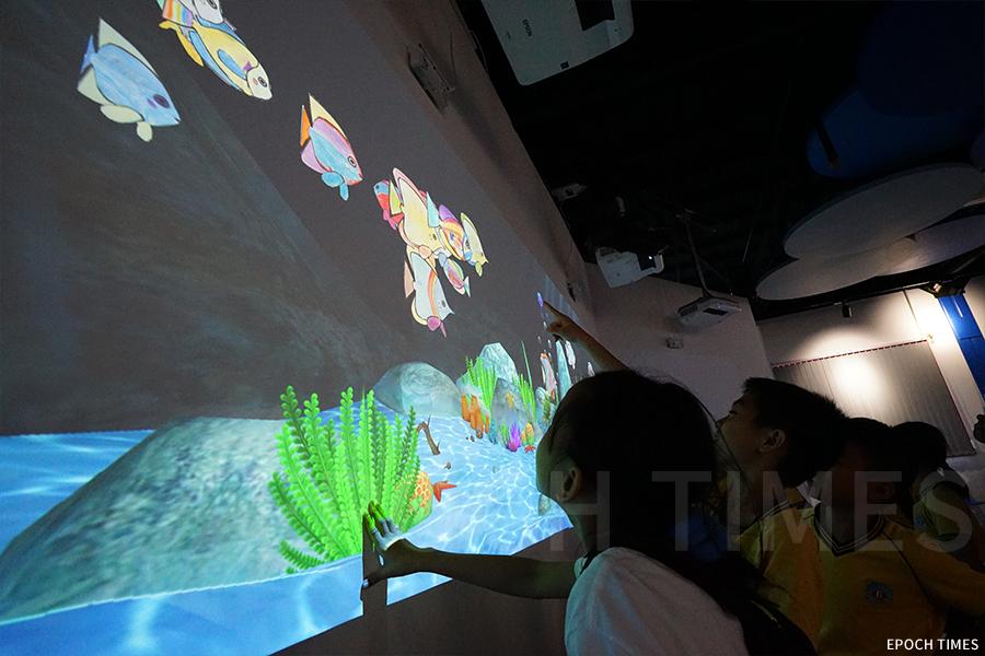 學生們興奮地看著自己畫的魚在虛擬魚缸中游動。(曾蓮/大紀元)