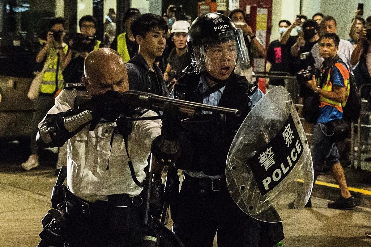 2019年7月30日,大批香港居民包圍葵涌警署,與警方發生對峙。一名警察舉起霰彈槍對準示威者,被指為危險動作。(ISAAC LAWRENCE/AFP/Getty Images)