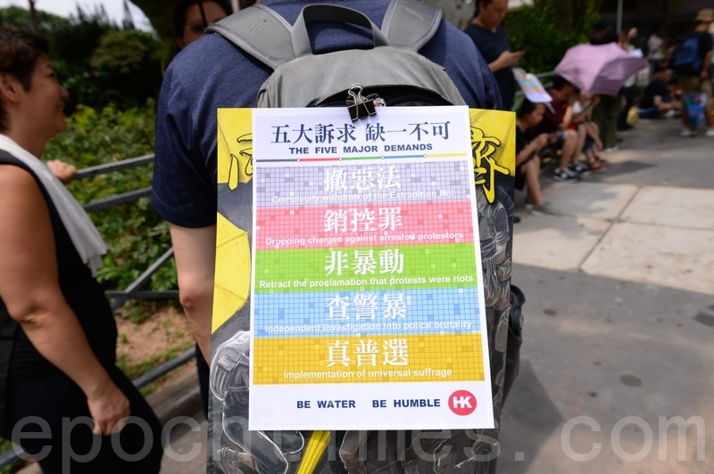 有市民在背包掛上重申五大訴求的海報。(宋碧龍/大紀元)