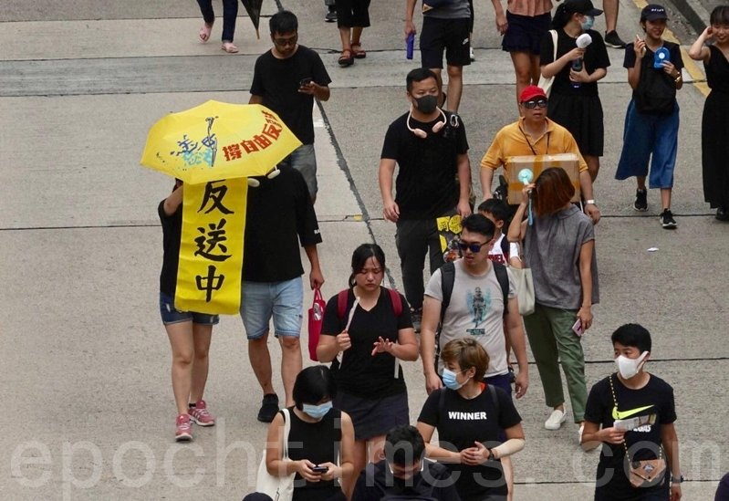 有參加深水埠遊行的市民舉起反送中標語。(余鋼/大紀元)
