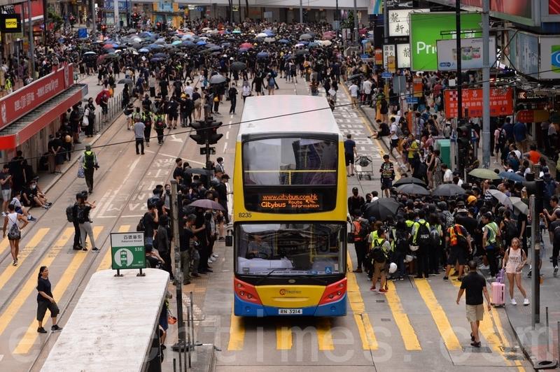 在港島,銅鑼灣崇光百貨對出的軒尼詩道,示威者散開兩邊巴士讓通過。(宋碧龍/大紀元)