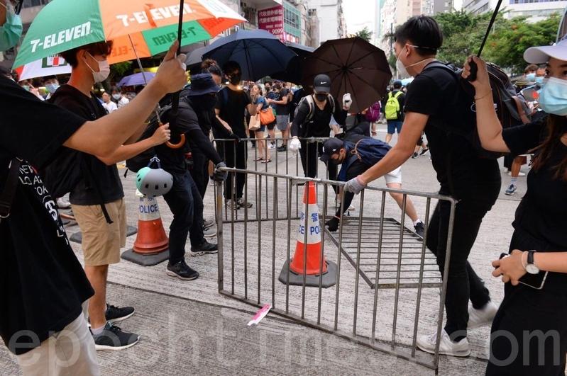 有示威者在遊行到軒尼詩道,接近灣仔修頓球場位置,架設障礙物封路。(宋碧龍/大紀元)