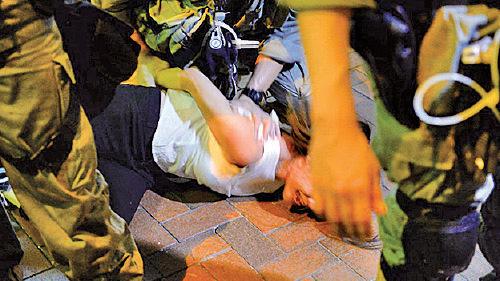 北角城市花園社區主任仇栩欣晚上近9時疑在拍攝直播遭警員制服在地,現場消息稱她涉襲警被捕。(宋碧龍/大紀元)