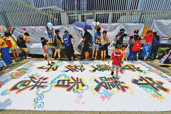 大批市民10日上午參加「守護孩子未來」親子遊行。不少父母帶同子女10 時半在中環愛丁堡廣場集合,當中不少爸媽手抱小孩子或推著嬰兒車出席。大會在廣場上放置空白橫額,提供顏料及顏色筆給小朋友在橫額上畫畫寫字,又派發氣球讓家長及小朋友在氣球上寫上訴求。參與者其後遊行至政府總部,並沿途高呼口號,包括「政府好懶惰,市民好難過」,「警察犯錯,就要改過」等。遊行人士抵達公民廣場外,在圍欄上掛上橫額及汽球表達訴求後和平散去。(王冬燕/大紀元)
