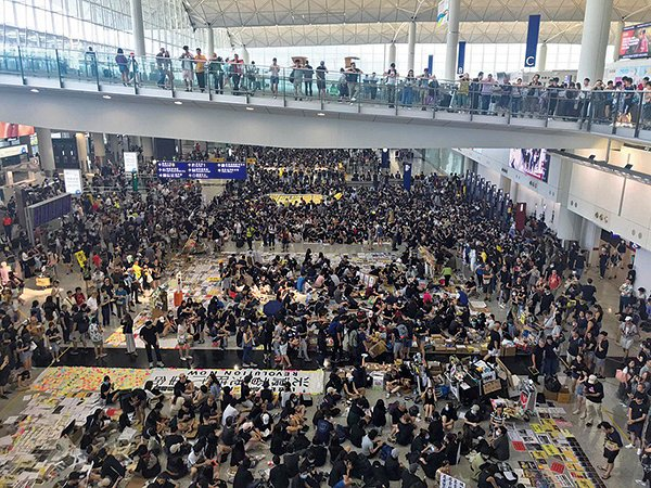 機場集會最搶眼的是地板鋪上巨型紙牌寫上「Welcome to the City of Expired Tear Gas」(歡迎來到過期催淚彈之城),暗示警方疑向人群發射過期催淚彈。(林卓楷/大紀元)