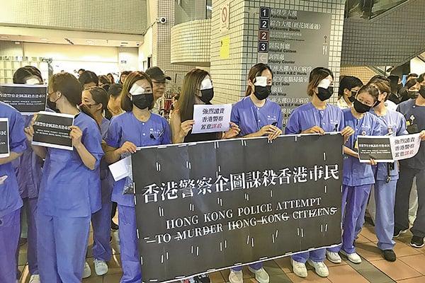 東區醫院昨日中午有醫護人員戴口罩又以紗布遮眼,抗議警方「企圖謀殺香港市民」。(網絡圖片)