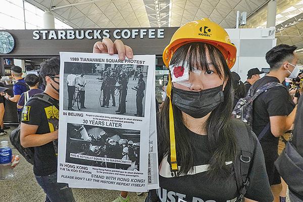 市民戴頭盔及用紗布遮眼,控訴警方近距離開槍致示威者失明。(余鋼/大紀元)
