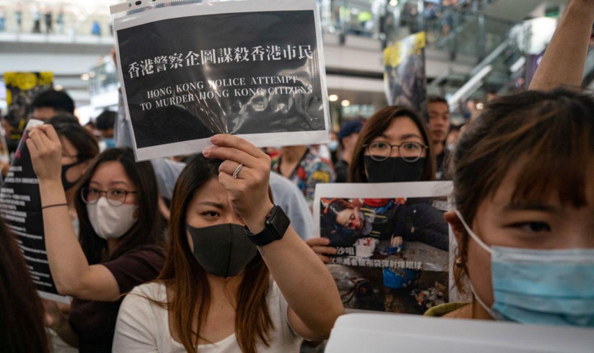 香港抗議者舉牌抗議香港警方8月11日晚射爆示威女子右眼,斥港警企圖謀殺市民。(Anthony Kwan/Getty Images)