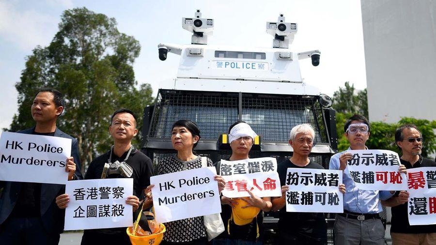 圖文8月12日,香港民主派立法會議員在港警準備動用的水炮車前舉牌抗議。(MANAN VATSYAYANA/AFP/Getty Images)