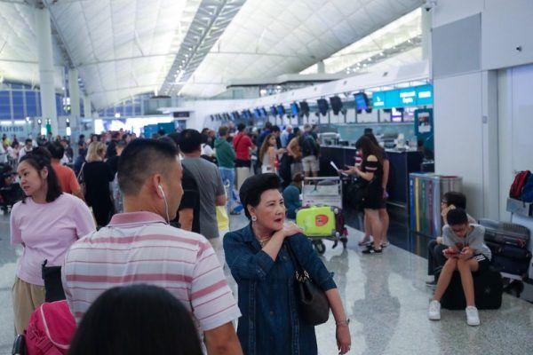 香港反送中示威者號召全民罷工、百萬人塞爆機場,造成香港機場12日下午4時起全數航班取消,13日班機航班大亂,旅客在櫃檯前排隊等候。(中央社)