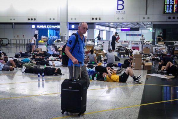 香港反送中示威者號召全民罷工、百萬人塞爆機場,造成香港機場12日下午4時起全數航班取消,13日清晨5時示威者剩不到百人,旅客在示威者身處的大廳穿梭。(中央社)