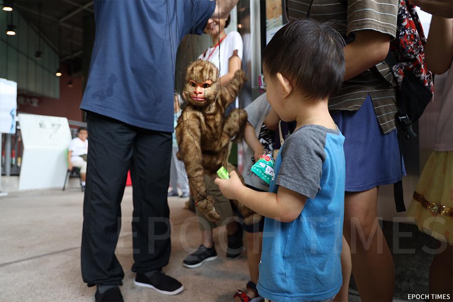 黃暉師傅受邀參與社區演出,與小朋友互動。(曾蓮/大紀元)