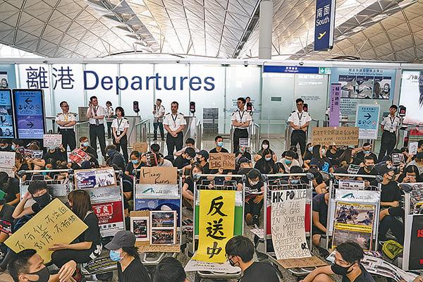 市民繼續到機場集會,並堵塞南面離境禁區閘口通道,高喊口號及舉標語。(Getty Images)