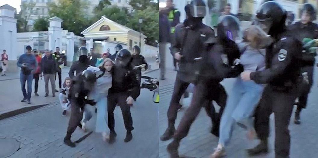 俄國一名女性示威者被鎮暴警察架住身子,其中一人竟握拳朝女子腹部重毆。(擷自網路)
