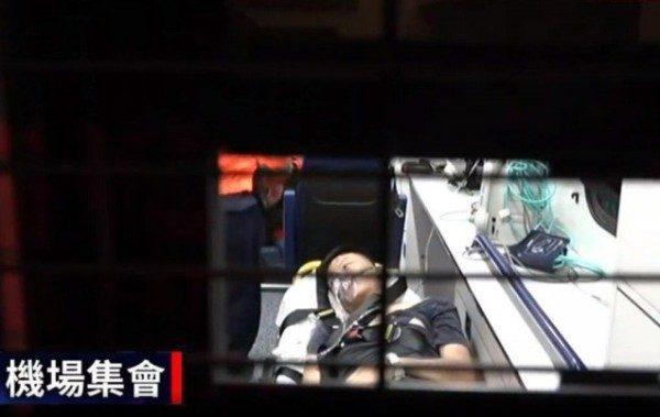 該名疑為中國公安男子被送上救護車後立即睜開眼睛。(圖片來源:香港《01》直播畫面)