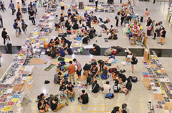機管局宣佈已獲法庭出臨時禁制令,仍有逾百示威者仍留接機大堂示威區。(宋碧龍/大紀元)