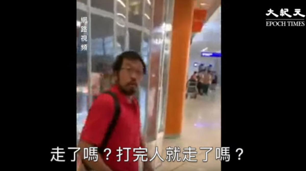 紅衣人踢打過黑衣人後一邊走向電梯,一邊與跟在他身後的抗議者對嗆。(影片截圖)