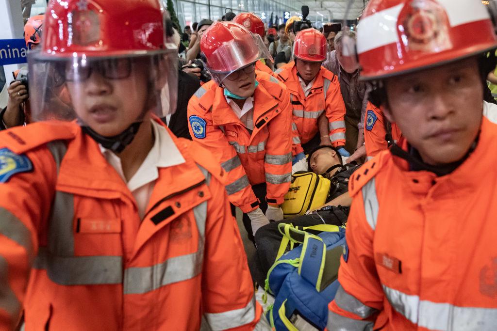 2019年8月13日,在中國香港國際機場舉行的一次示威活動中,一名被懷疑為中共臥底警察的男子被醫務人員帶走。(Anthony Kwan/Getty Images)