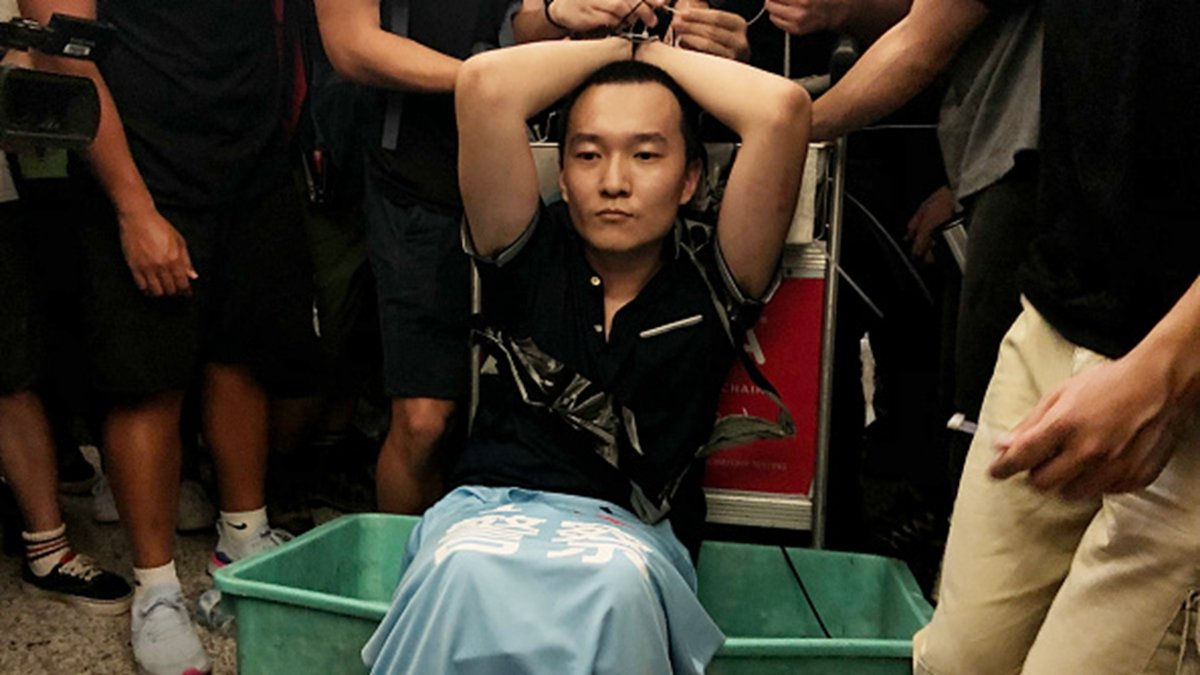 8月13日,中共黨媒一名記者在香港機場被民眾抓住,他隨身攜帶一件寫有「我愛警察」的藍色T恤,和香港街頭打人的黑幫分子是同款,引發民眾憤怒。(Anthony Kwan/Getty Images)