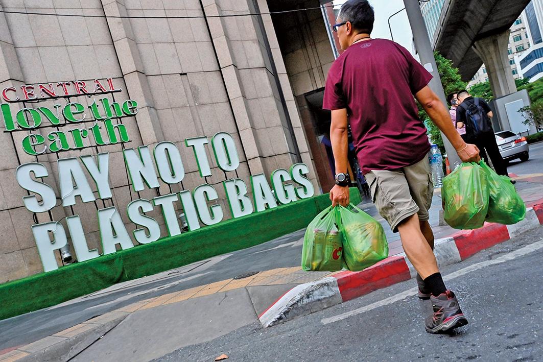 最近,美國一些城市降下「塑料雨」。目前,美國一些城市禁用膠袋。圖為一雙手拎著膠袋的男子走過「對膠袋說『不』」的標語。(AFP)