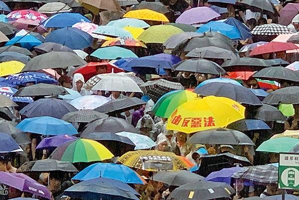 圖為昨日民陣反送中遊行隊伍中,有市民打開寫有「撐自由反惡法」的黃雨傘。( 駱亞/大紀元)