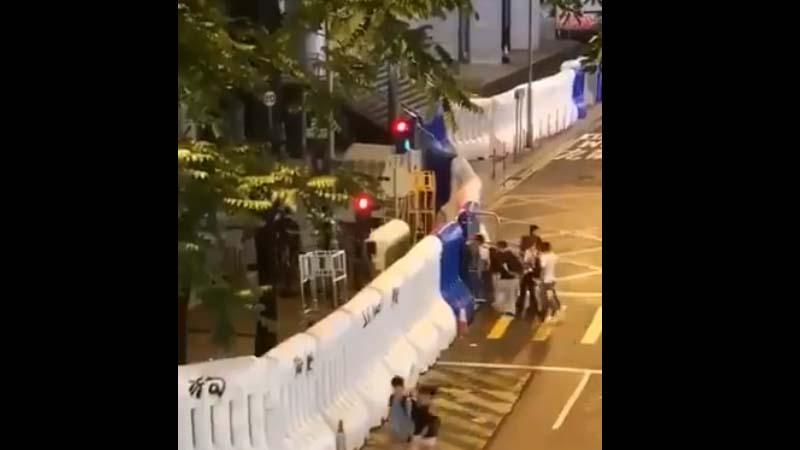 圖為8月18日午夜清場結束後,一批示威者打扮的人士步入有水馬防護的香港警察總部。(影片截圖)