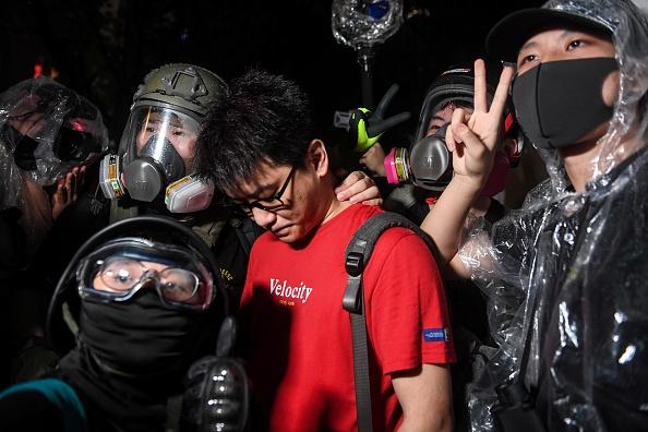 8月18日晚,一名身穿紅色T恤、說普通話的大陸男子,被香港示威者識破身份。但此次港人的處理方式與上次大不相同,贏得網民點讚「有智慧」。(LILLIAN SUWANRUMPHA/AFP/Getty Images)