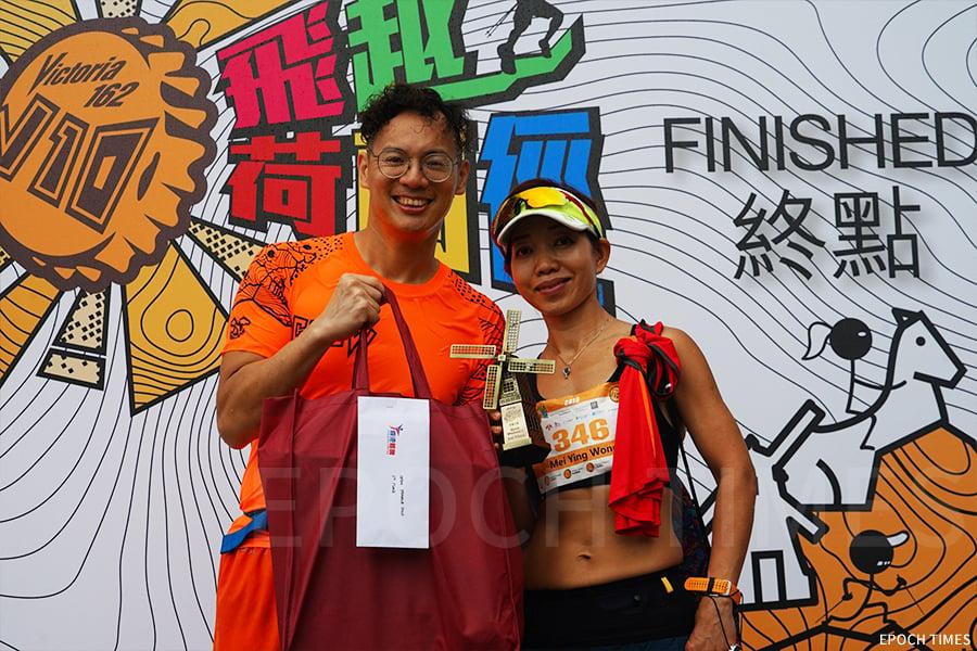賽事總監Matthew Mok(左)為女子公開組第一名獲獎跑手黃美英頒獎。(曾蓮/大紀元)