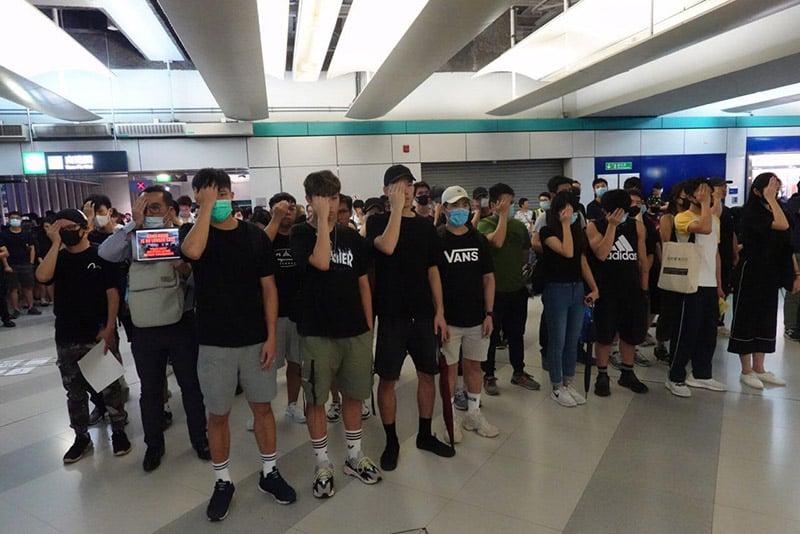 靜坐人士默站呼籲市民毋忘「元朗恐襲」,又用手蓋住自己右眼,聲援8月11日右眼中彈的的女急救員。(余鋼/大紀元)