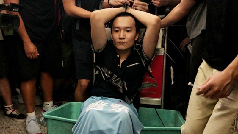 8月13日,中共黨媒《環球時報》記者付國豪在香港機場被民眾抓住,他隨身攜帶一件寫有「我愛警察」的藍色T恤,和香港街頭打人的黑幫分子是同款,引發民眾憤怒。(Anthony Kwan/Getty Images)