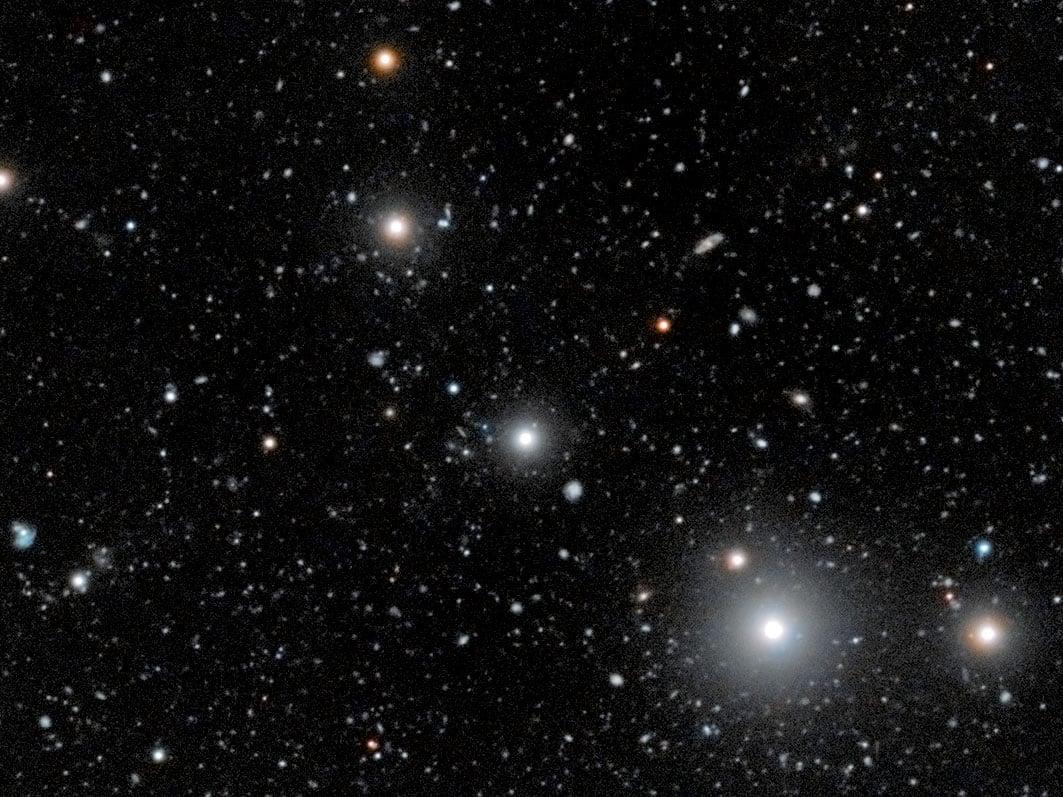 該圖像結合了來自超大望遠鏡的觀測結果,由Digitized Sky Survey 2中的顏色數據檢測出由類星體照射黑暗星系所產生的螢光發射。(ESO)
