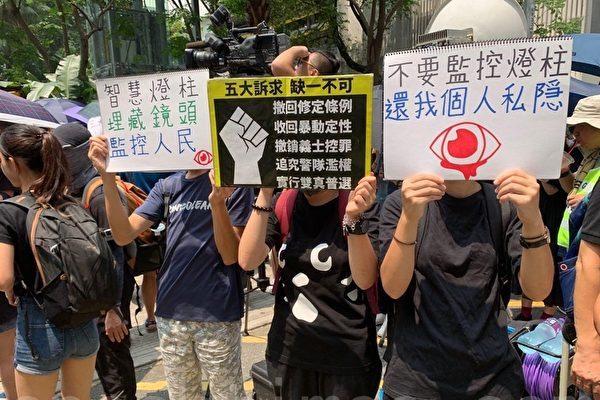 8月24日,在觀塘駿業公園人們等待遊行,現場民眾舉著寫有「不要監控燈柱 還我個人隱私」、「五大訴求 缺一不可」、「智慧燈柱 埋藏鏡頭 監控人民」等標語表達心聲。(駱亞/大紀元)