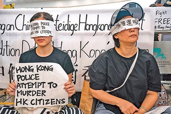8月12日,市民發起「黑警還眼」運動,在香港國際機場靜坐,並向乘客介紹反送中運動。(Getty Images)