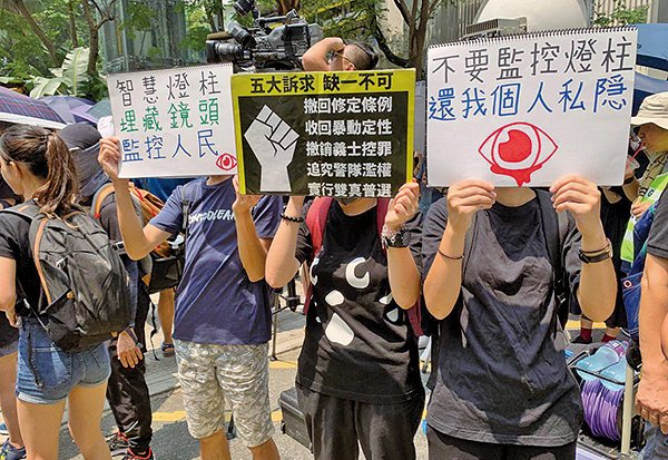 8月24日,在觀塘駿業公園民眾舉著寫有「不要監控燈柱 還我個人私隱」、「智慧燈柱 埋藏鏡頭 監控人民」等標語表達心聲。(駱亞/大紀元)