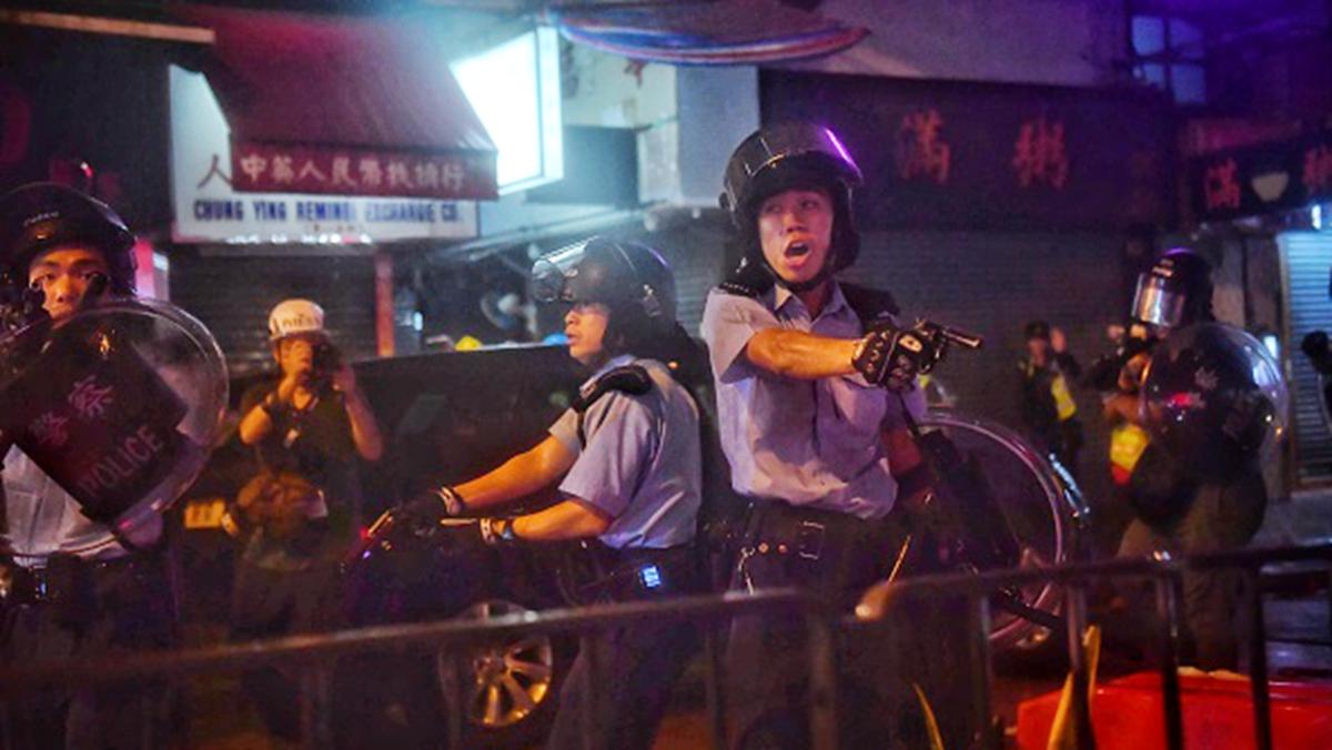 8月25日晚,一名香港警察舉起手槍對準示威者和記者。 (LILLIAN SUWANRUMPHA/AFP/Getty Images)