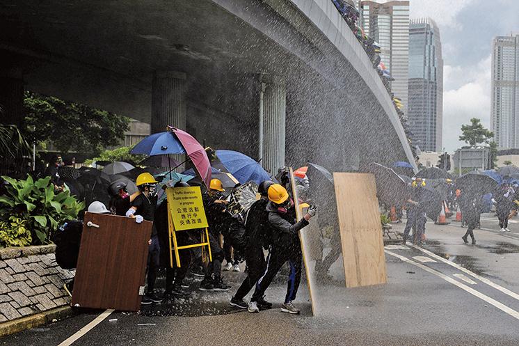 美國CBS新聞記者英若明(Ramy Inocencio)記錄的香港8月31日抗議活動。圖為8月31日香港抗議者在用雨傘等抵制警方水炮車發射的水柱。(Getty Images)