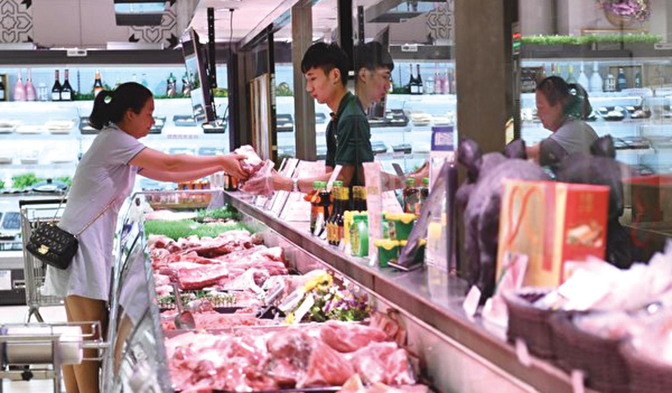 北京9月1日對美豬徵高關稅後,未來大陸豬肉價仍會保持在高位。圖為北京一超市內市民購買豬肉。(大紀元資料室)