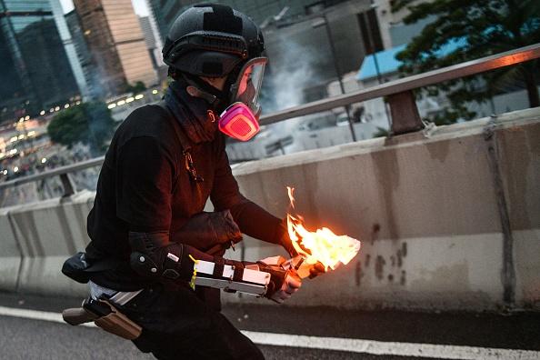 投擲汽油彈的黑衣人被拍到腰別警用手槍。 (ANTHONY WALLACE/AFP/Getty Images)