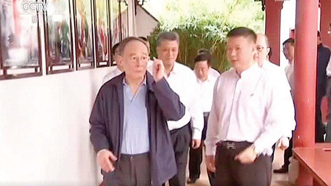 王岐山(左)廣東「調研」,牆上的畫顯然不是他關注的焦點。(影片截圖)