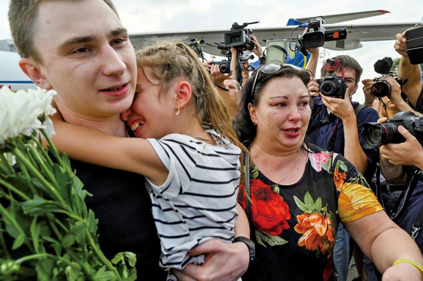 返回烏克蘭的35名囚犯與親友相擁而泣。(AFP)