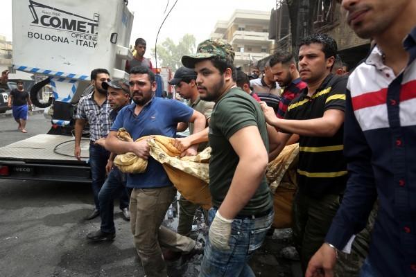 伊拉克首都巴格達上周末(2日)晚間發生的汽車炸彈爆炸案,死亡人數已經攀至250人。圖為7月4日,參與救難的人員運送罹難者遺體。(AHMAD AL-RUBAYE/AFP)
