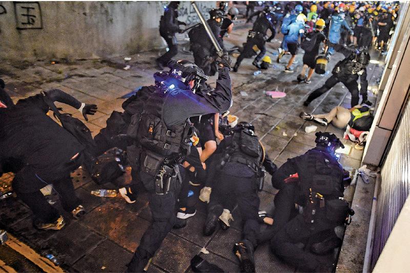 8月11日,一名在銅鑼灣僥倖逃脫的示威者W,日前對媒體講述警察喬裝「示威者」毆打及抓捕「同伴」的經過。這些警員身上飾有藍色LED,均持有伸縮警棍,部份人更被媒體拍攝到還配備槍械。(MANAN VATSYAYANA/AFP/Getty Images)