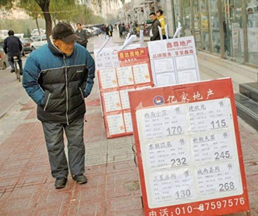 圖為北京一市民在房產中介門口看房屋價格牌。(Getty Images)