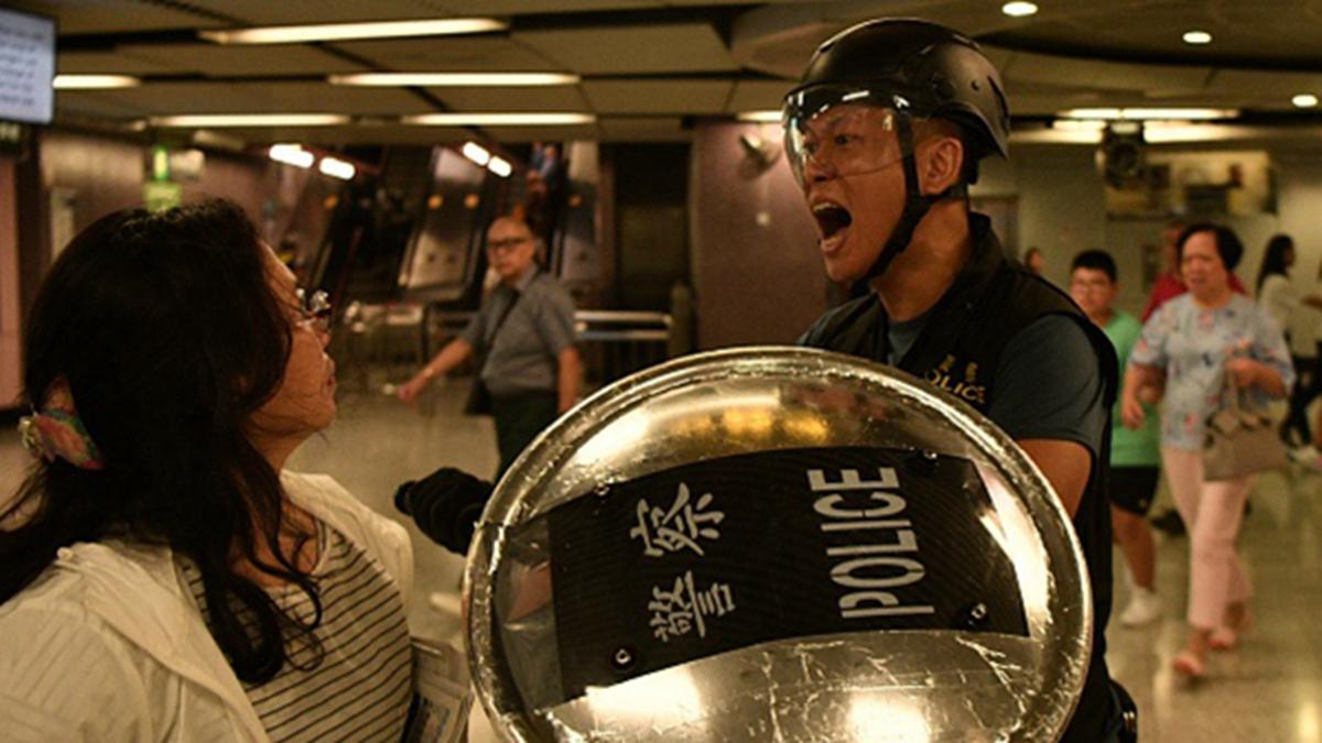 疲於「反送中」,10日港警配發一萬支警棍,容許下班警員隨身攜帶,意味著警察將24小時處於待命。然而「反送中」正贏得更多港人的支持,不少警嫂也是抗議者,甚至在街頭與丈夫對峙。(ANTHONY WALLACE/AFP/Getty Images)