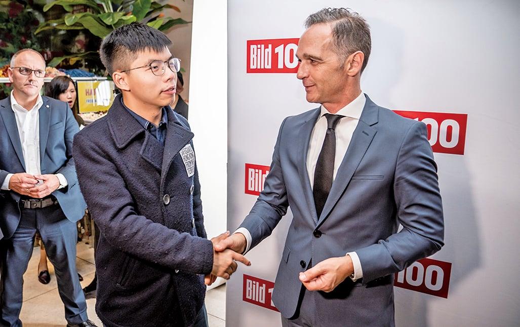黃之鋒(左)與德國外長馬斯(右)交談。(AFP)
