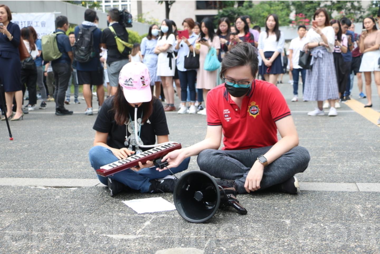 在繼《願榮光歸於香港》這首歌曲第一次隆重出場後,今日(9月13日)下午1時,來自香港各界的白領一族數百人齊聚中環遮打花園進行同步快閃合唱此首歌曲,並持續要求「五大訴求,缺一不可」,圖為木琴演奏者在演奏。(葉依帆 / 大紀元)
