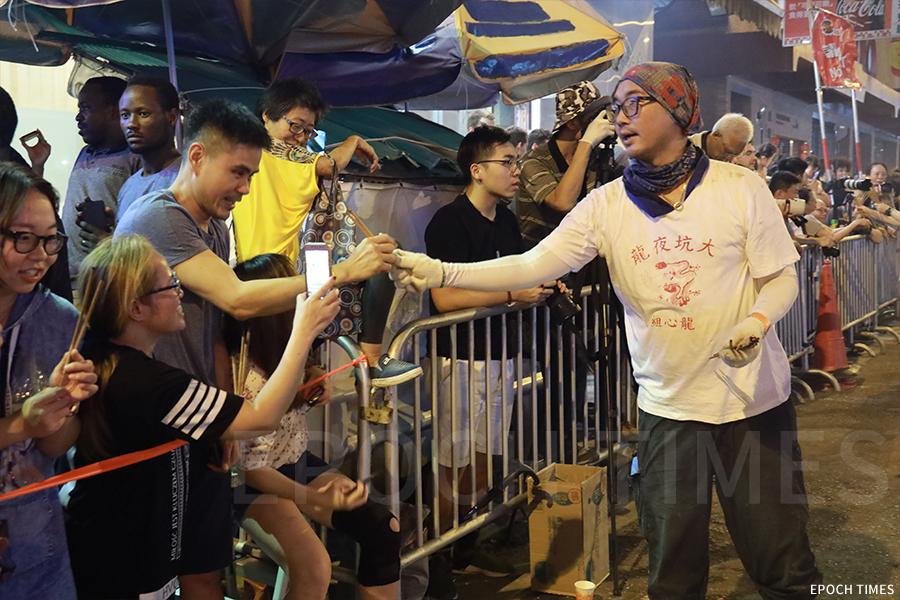 工作人員為觀賞市民派發香枝。(陳仲明/大紀元)